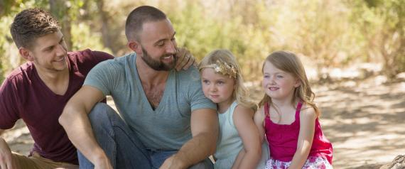 Male couple sitting on riverbank with two daughters